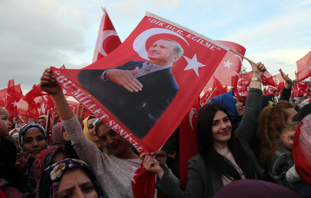 "Supporters of the ""yes"" vote wave Turkish National flags and flags depicting Turkish president Recep Tayyip Erdogan as they cheer during his speech at the Presidential Palace in Ankara, on April 17, 2017, following the results in a nationwide referendum. (Adem Altan/AFP/Getty Images)"
