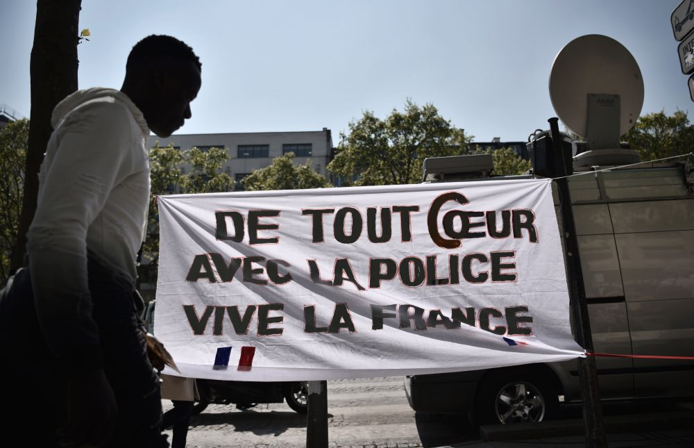 """A man walks by a poster with an inscription which translates as """"With all my heart with the police, Long live France"""" on the Champs Elysees in Paris on April 21, 2017, a day after a gunman opened fire on police on the avenue, killing a policeman and wounding two others in an attack claimed by the Islamic State group just days before the first round of the presidential election. (Philippe Lopez/AFP/Getty Images)"""