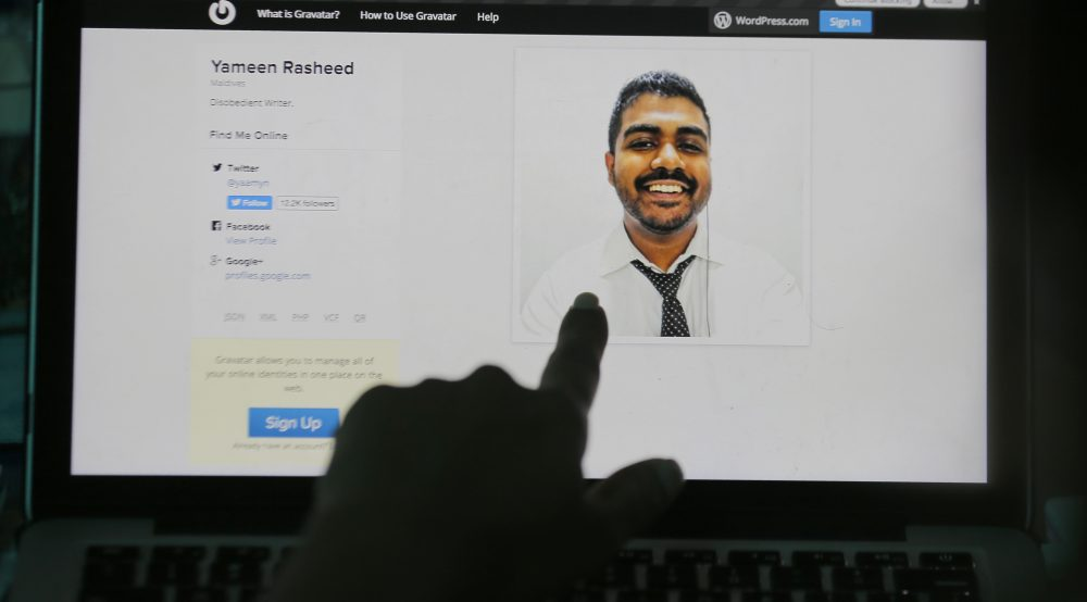 """A Sri Lankan woman points to a portrait of Maldivian blogger Yameen Rasheed on his blog """"The Daily Panic"""" in Colombo, Sri Lanka, Sunday, April 23, 2017. Police in the Maldives said in a statement that Rasheed was found Sunday morning with multiple stab wounds in a house in the capital, Male. He died at a hospital. (Eranga Jayawardena/AP)"""