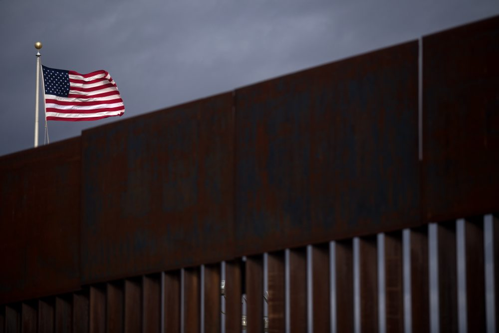 A U.S. flag flies near section of the border fence on the U.S.-Mexico border in Agua Prieta, Sonora, Mexico, in 2017. (Guillermo Arias/AFP/Getty Images)