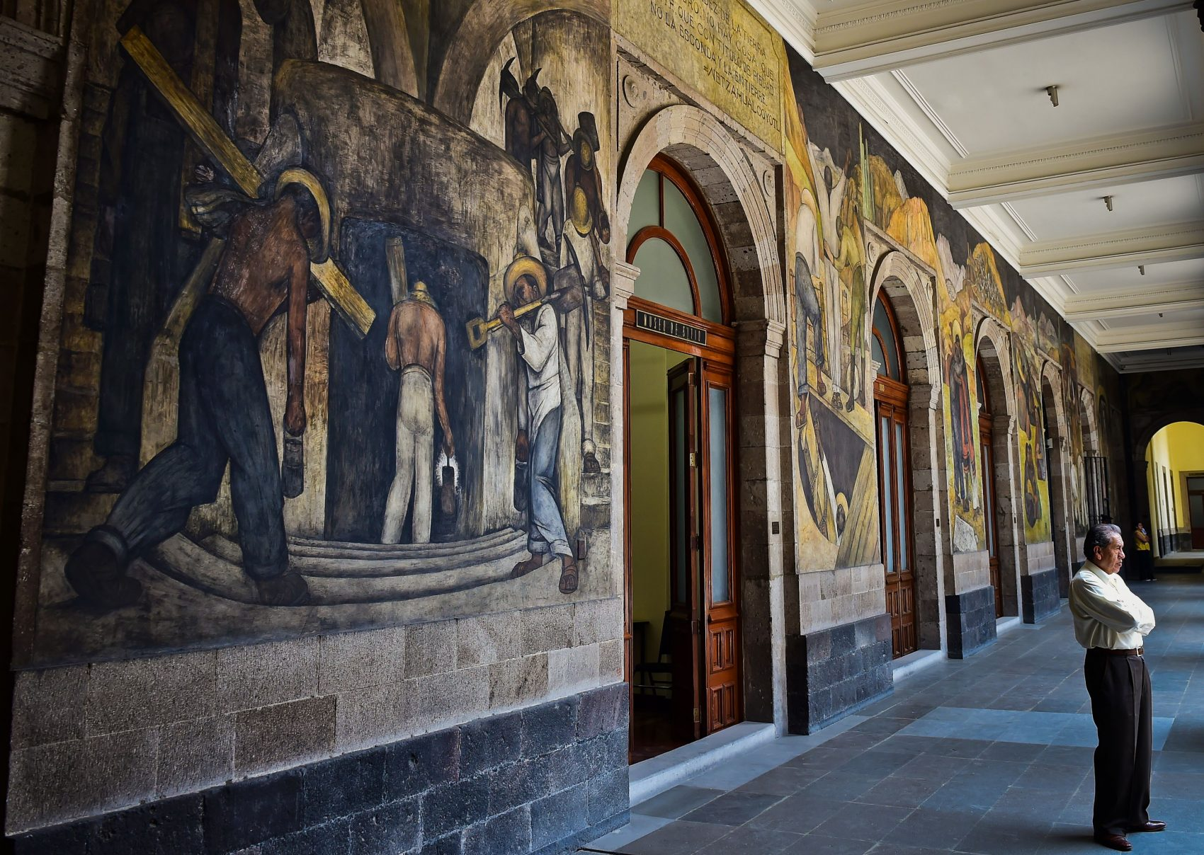 A man stands next to murals by Mexican artist Diego Rivera in the Education Secretariat in Mexico City on April, 6, 2017.  Rivera was the most visible figure in Mexican muralism, a large-scale public art initiative that emerged in the 1920s in the wake of the Mexican Revolution. (Ronaldo Schemidt/AFP/Getty Images)