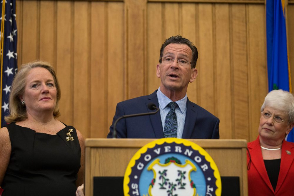 Connecticut Gov. Dannel Malloy, joined by his wife, Cathy Malloy, left, and Lt. Gov. Nancy Wyman, announced at a press conference Thursday that he would not seek a third term. (Ryan Caron King/WNPR)