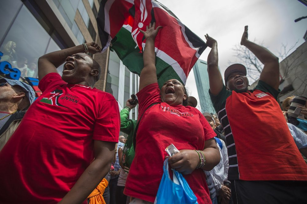 From left, Kenyan fans John Githaiga, of Kenya, and Penny Waweru and Frank Githinji, of Lowell, cheer as Edna Kiplagat crosses the finish line to win the women's race. (Jesse Costa/WBUR)