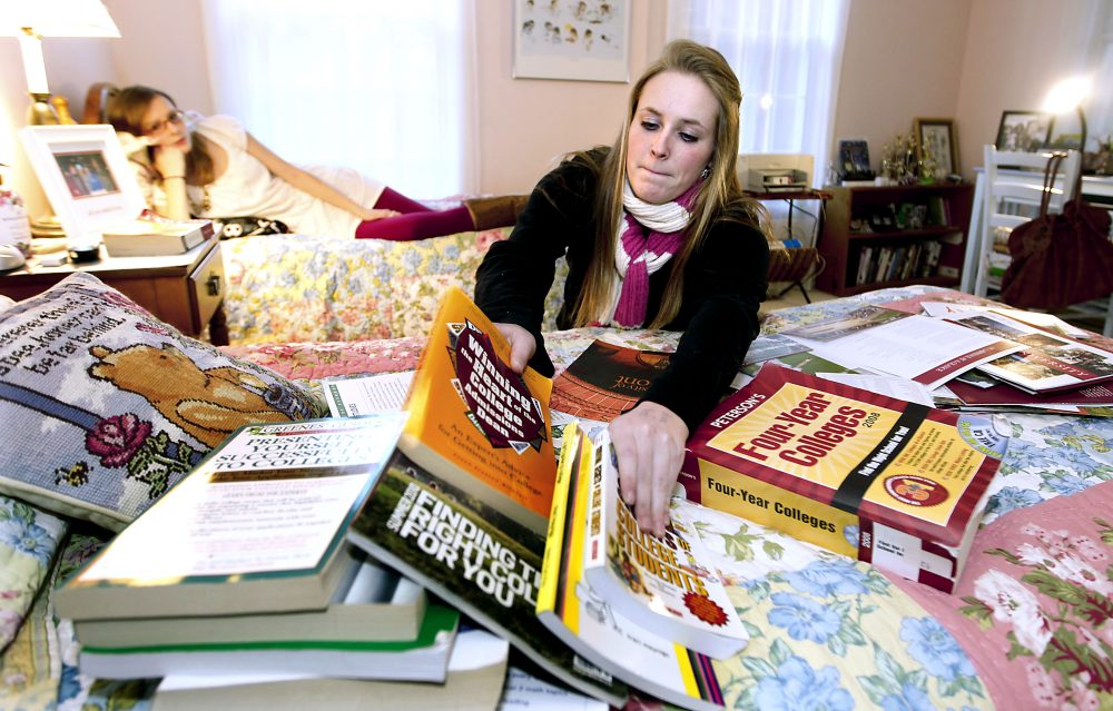 In this Thursday, Nov. 11, 2010 photo, Kim Pollock, 17, facing center, goes through college materials, as her sister Lindsay, 15, back left, watches, in her bedroom in Bedford, N.H.  (AP Photo/Cheryl Senter)