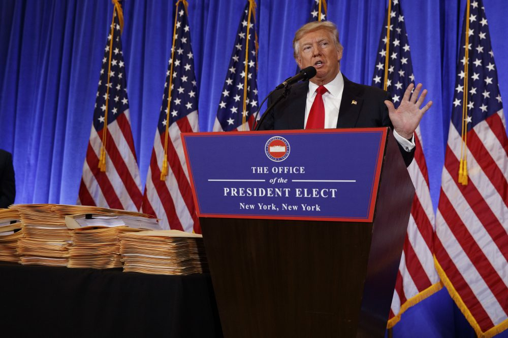 Then-President-elect Donald Trump speaks during a Jan. 11 news conference next to a stack of folders that he said contained documentation separating him from his businesses. (Evan Vucci/AP)