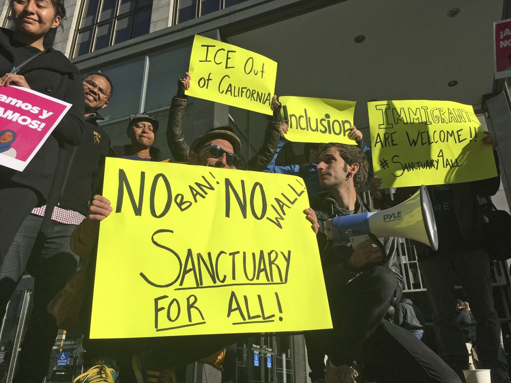 The president's tactics remind C. Nicholas Cuneo of those of Robert Mugabe, Zimbabwe's brutal dictator. Pictured: Protesters hold up signs outside a courthouse where a federal judge heard arguments in the first lawsuit challenging President Donald Trump's executive order to withhold funding from communities that limit cooperation with immigration authorities Friday, April 14, 2017, in San Francisco. U.S. District Court Judge William Orrick temporarily blocked the Trump administration from cutting off funds to any of the nation's so-called sanctuary cities. (Haven Daley/AP)
