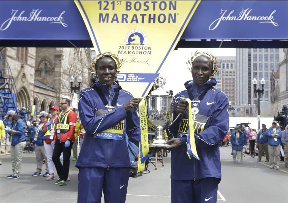 Edna Kiplagat, left, and Geoffrey Kirui, both of Kenya, hold a trophy together after their victories in the 121st Boston Marathon. (Elise Amendola/AP)