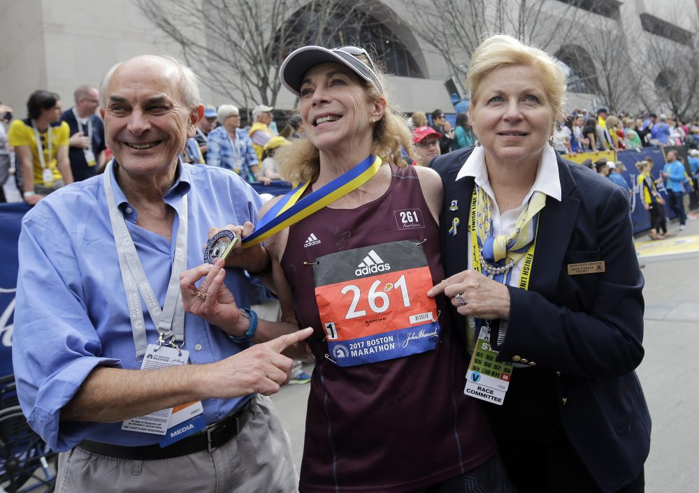 Kathrine Switzer, center, the first official woman entrant in the Boston Marathon 50 years ago, wears the same bib number after finishing the marathon on Monday. With Switzer are her husband Roger Robinson, left, and Joann Flaminio, right, of the Boston Athletic Association. (Elise Amendola/AP)