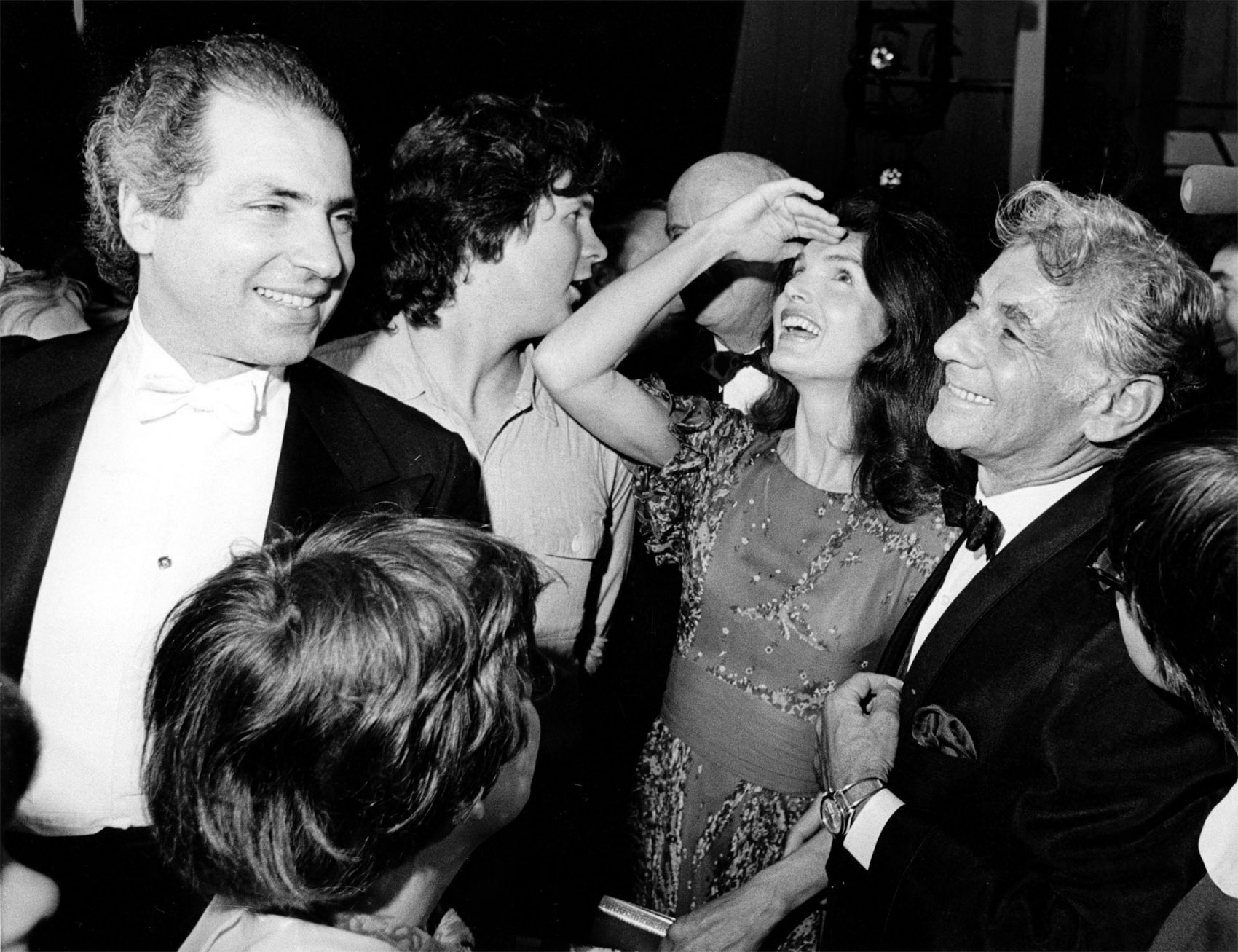 "Jacqueline Kennedy Onassis shields the light from her eyes as she looks up at the stage in Washington's John F. Kennedy Center for the Performing Arts on June 5, 1972. With her is conductor-composer Leonard Bernstein, who wrote ""Mass"" for the opening of the cultural center. (AP)"