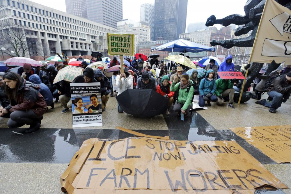 Demonstrators kneel for a moment of silence outside the JFK Federal Building, Monday, March 27, 2017, in Boston, as they protest the detention by federal immigration officials of two advocates for Vermont dairy farm workers, as well as an undocumented Vermont farm worker. (Elise Amendola/AP)