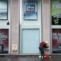 A worker cleans a sign outside the Fox television studios, where a poster of Bill O'Reilly has been removed, in New York.  (Richard Drew/AP)