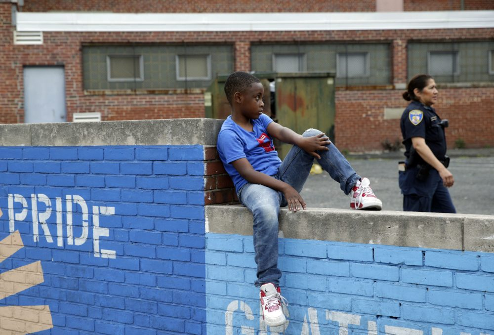 Sessions' recent directive to his Department of Justice grants local police sole sway in how they interact with communities of color, without civilian input, writes Kevin C. Peterson. Pictured here: A boy sits on a wall as a member of the Baltimore Police Department walks by in the Penn North neighborhood of Baltimore, June 2016, near the site of unrest following the funeral of Freddie Gray. (Patrick Semansky/AP)