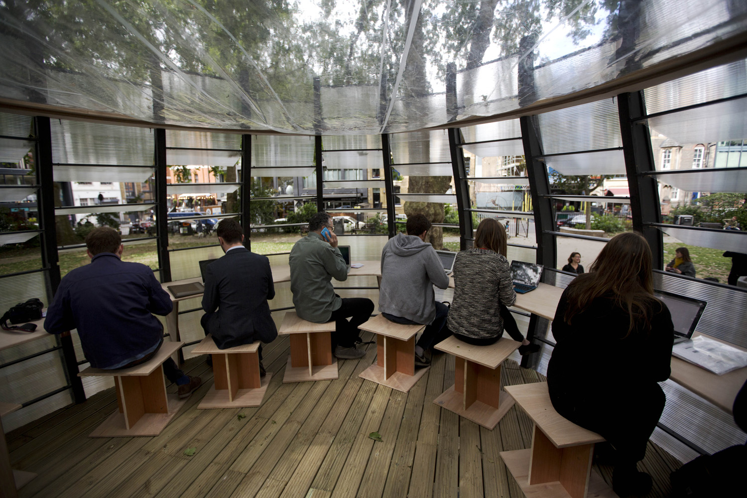 People pose for the media and work during an event to launch TREExOFFICE, a prototype pop-up tree office, in Hoxton Square, London. (Matt Dunham/AP)