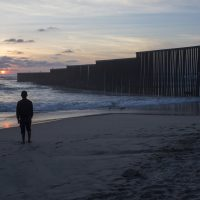 Someone needs to tell the President Trump and Congress a boat can go around a wall, a tunnel can go under a wall and a plane can go over a wall, writes comedian Jimmy Tingle. Pictured: A man stands on the shore of the Pacific Ocean by the US-Mexico border fence that separates Tijuana, Mexico, from San Diego, Calif. (Rodrigo Abd/AP)