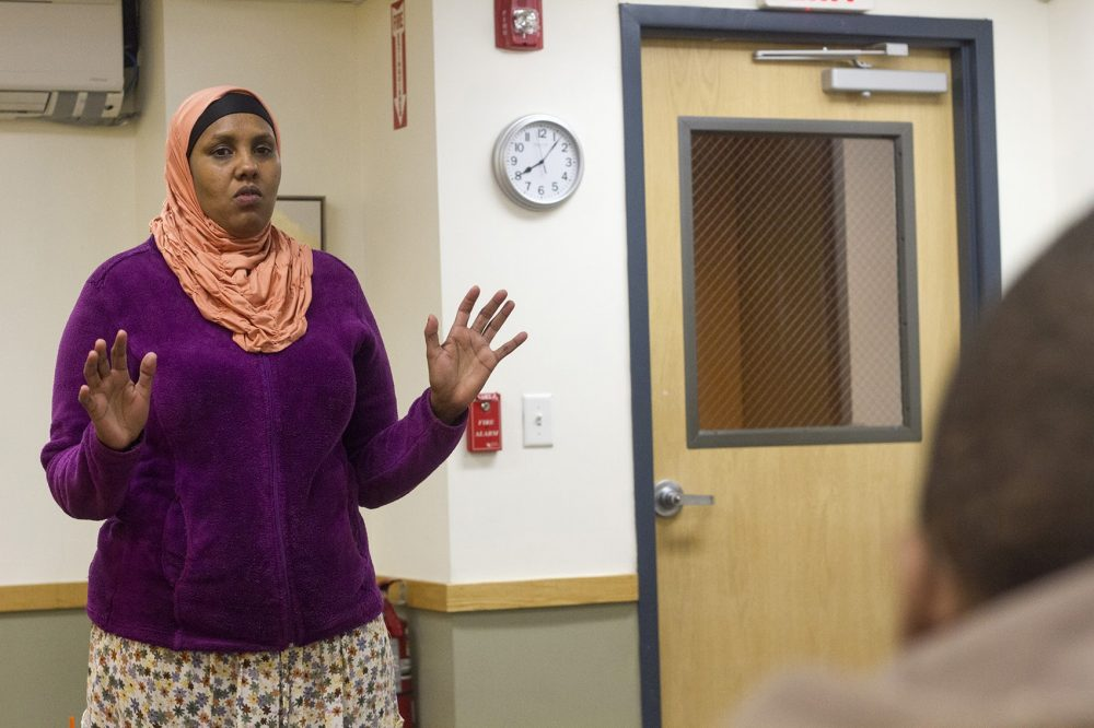 Sulekha Ali, a 37-year-old Somali refugee and mother of five, stands in front of the group and practices telling her own story. (Joe Difazio for WBUR)