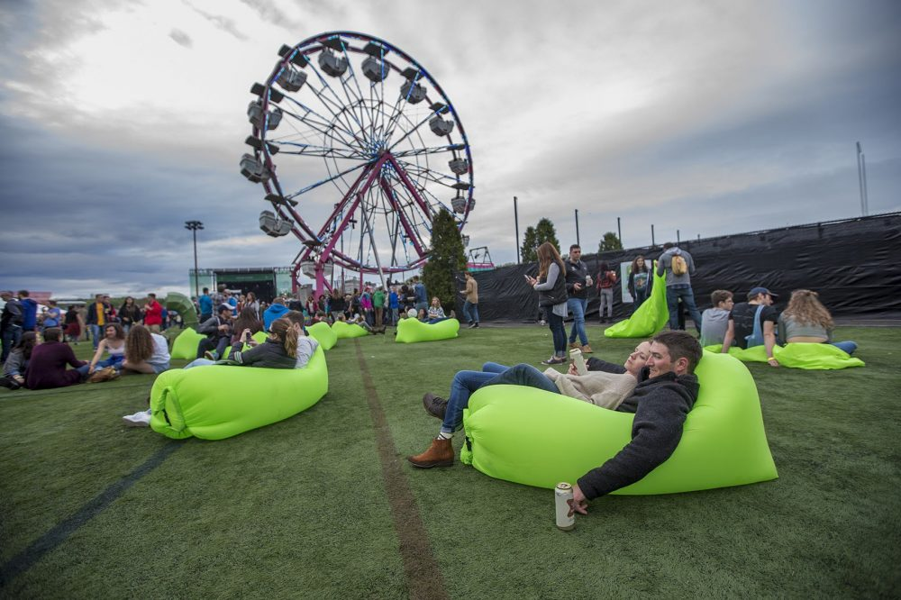 Brendan Legg and Jamie Toner relax in an air hammock at Boston Calling. This year, the festival is spreading across 16 acres in Allston, compared to just six at previous festivals in City Hall Plaza. (Jesse Costa/WBUR)