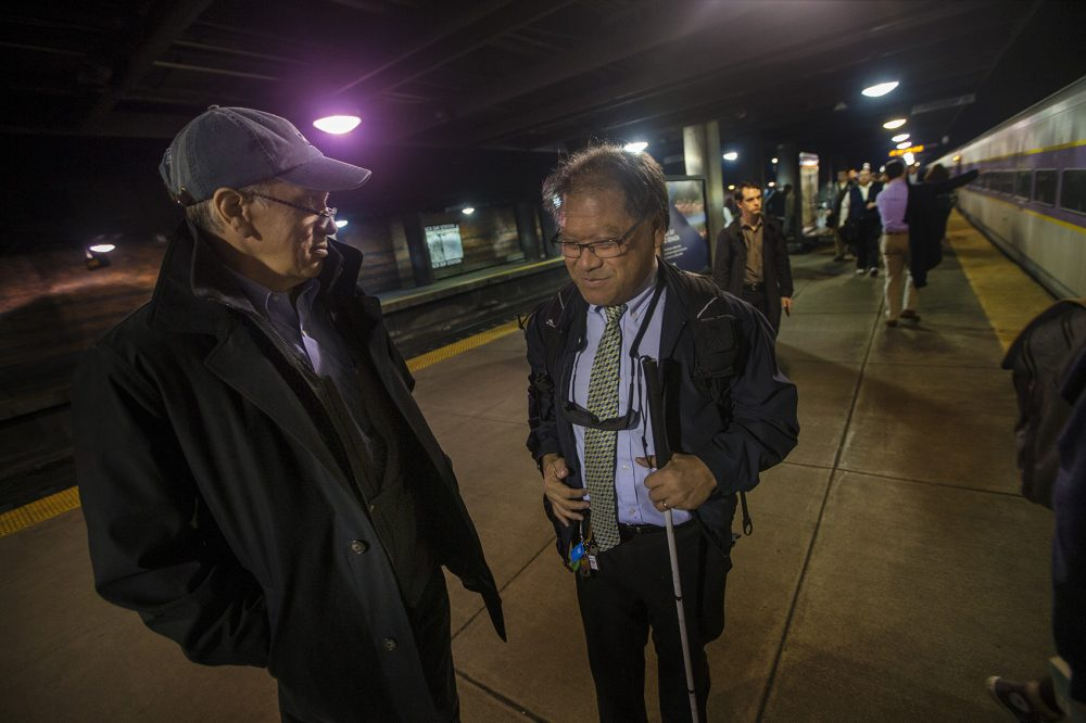 David Hill, left, meets Blair Wong on the platform in Back Bay station to help guide him. (Jesse Costa/WBUR)