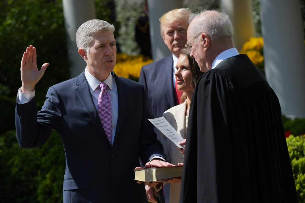 President Trump (second from left) watches as Justice Anthony Kennedy (right) administers the oath of office to Neil Gorsuch as an associate justice of the U.S. Supreme Court in the Rose Garden of the White House on April 10, 2017, in Washington, D.C., as Gorsuch's wife, Louise Gorsuch, looks on. (Mandel Ngan/AFP/Getty Images)