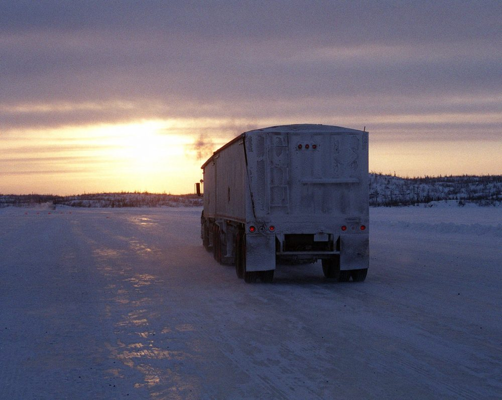 A truck heads toward the sunset on the Lupin winter road in Canada's Northwest Territories in 2001. (Bob Green/AP)
