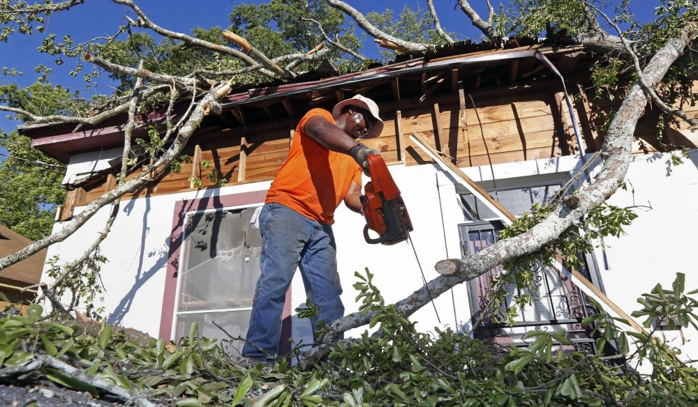 Pastor Michael Williams cuts branches from a wind-blown tree on Monday, May 1, 2017, that fell on a family member's home in Durant, Miss. (Rogelio V. Solis/AP)