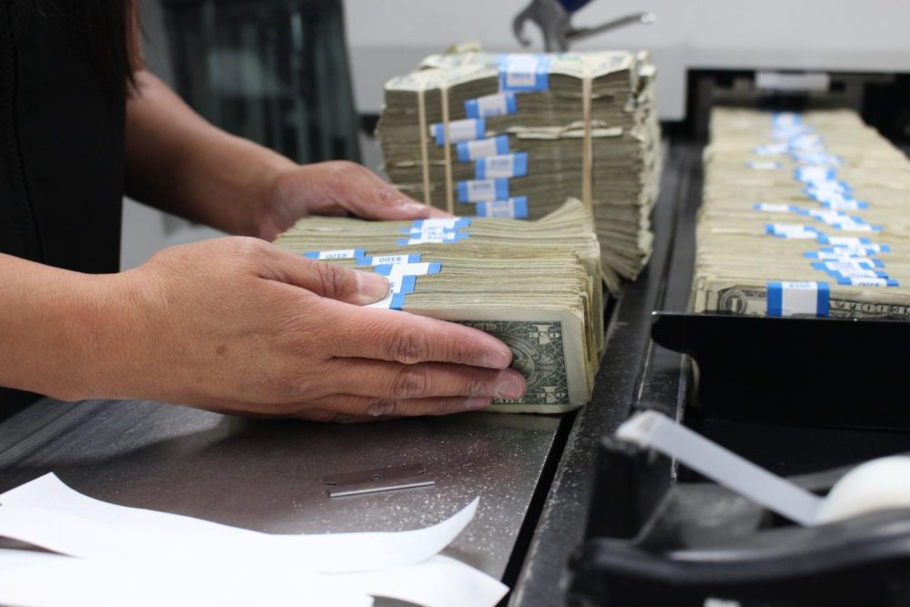 An employee prepares to feed currency into a machine at the Phoenix Processing Center. (Courtesy of the Federal Reserve)