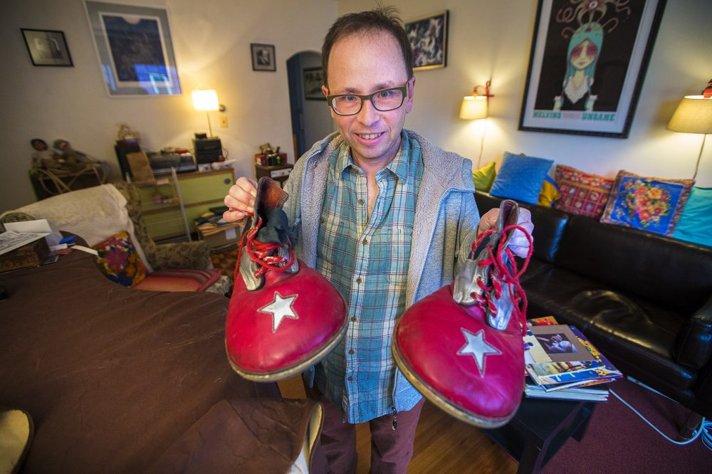 Peter Bufano holds the clown shoes he wore during his tenure as a clown with the Ringling Bros. and Barnum & Bailey Circus. (Jesse Costa/WBUR)