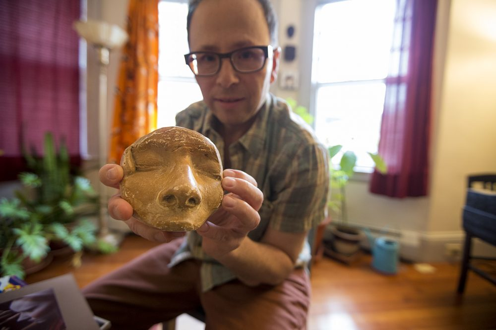 Peter Bufano holds a plaster mold of his face which was used to create his clown nose for circus shows. (Jesse Costa/WBUR)