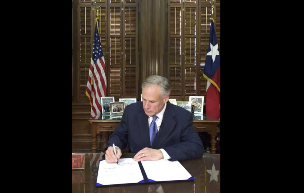 "In this Sunday, May 7, 2017 frame from video posted by the Office of the Governor, Republican Gov. Greg Abbott signs a so-called ""sanctuary cities"" ban in Austin Texas. The ban lets police ask during routine stops whether someone is in the U.S. legally and threatens sheriffs with jail if they don't cooperate with federal immigration agents. (Office of Gov. Abbott via AP)"