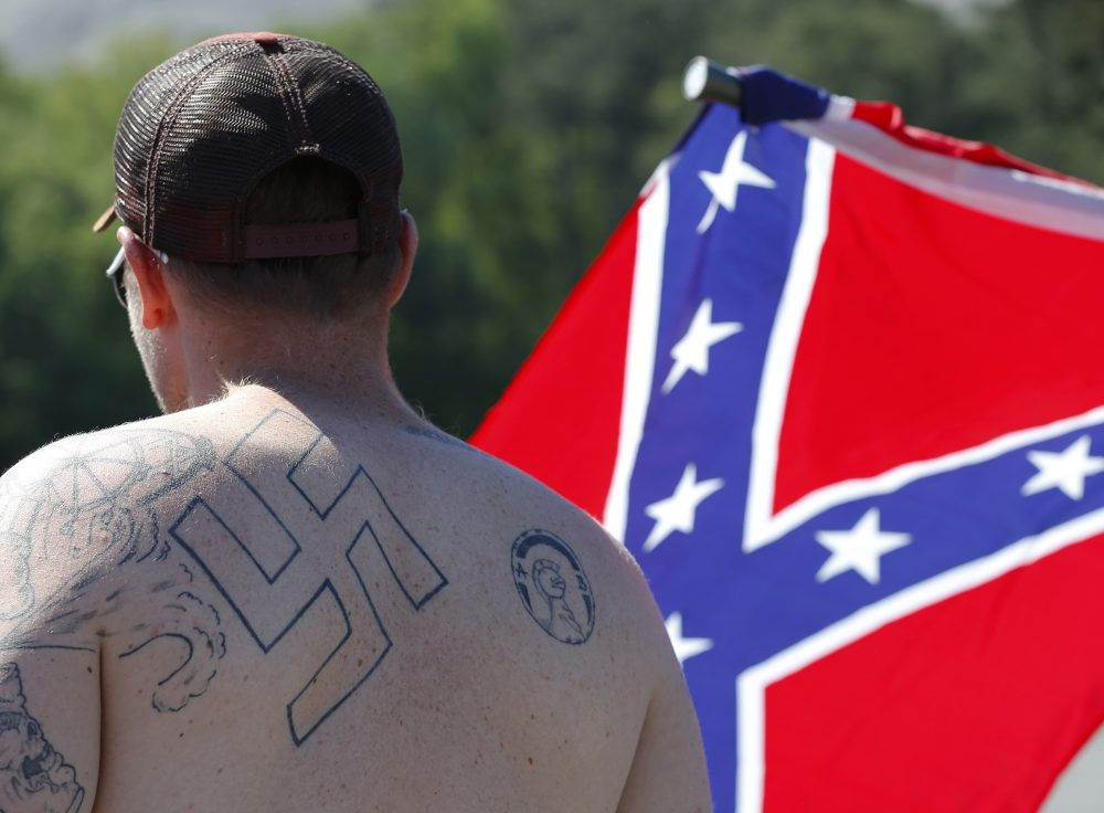 In this April 23, 2016 file photo, a man walks during a protest at Stone Mountain Park, in Stone Mountain, Ga. The Southern Poverty Law Center has filed a lawsuit against Andrew Anglin, founder of the white supremacist website The Daily Stormer, alleging that he orchestrated a campaign of online harassment against Montana real estate agent Tanya Gersh, her husband and their 12-year-old son. (John Bazemore/AP)