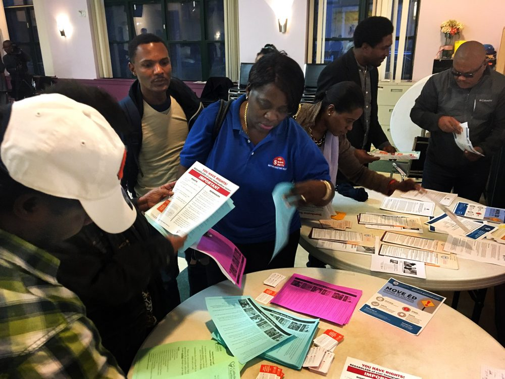 Attendees at a recent community forum collect handouts with information on immigration services. Many members of Boston's Haitian community are worried about the fate of their Temporary Protected Status which enables them to live and work in the U.S. (Shannon Dooling/WBUR)