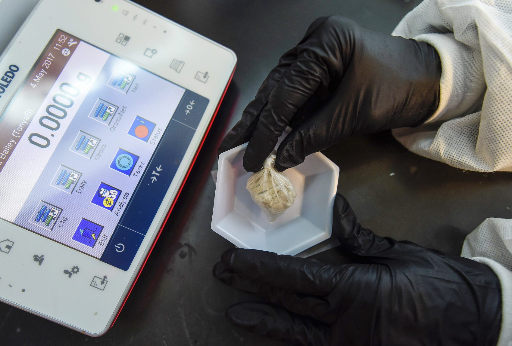 "A forensic chemist prepares a sample of the drug ""gray death"" to be weighed at the crime lab of the Georgia Bureau of Investigations in Decatur, Ga., on Thursday, May 4, 2017. The new and dangerous opioid combo underscores the ever-changing nature of the U.S. addictions epidemic. (Mike Stewart/AP)"
