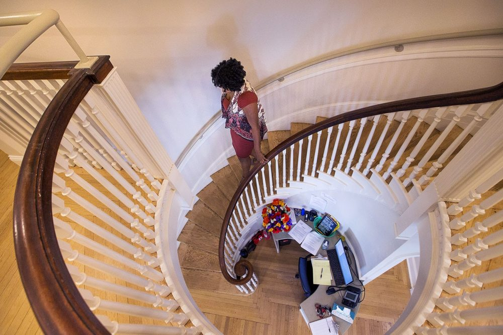 Nikita Coney, house manager at New Joelyn's Home, walks down the spiral staircase toward the reception area in the center of the house. (Jesse Costa/WBUR)