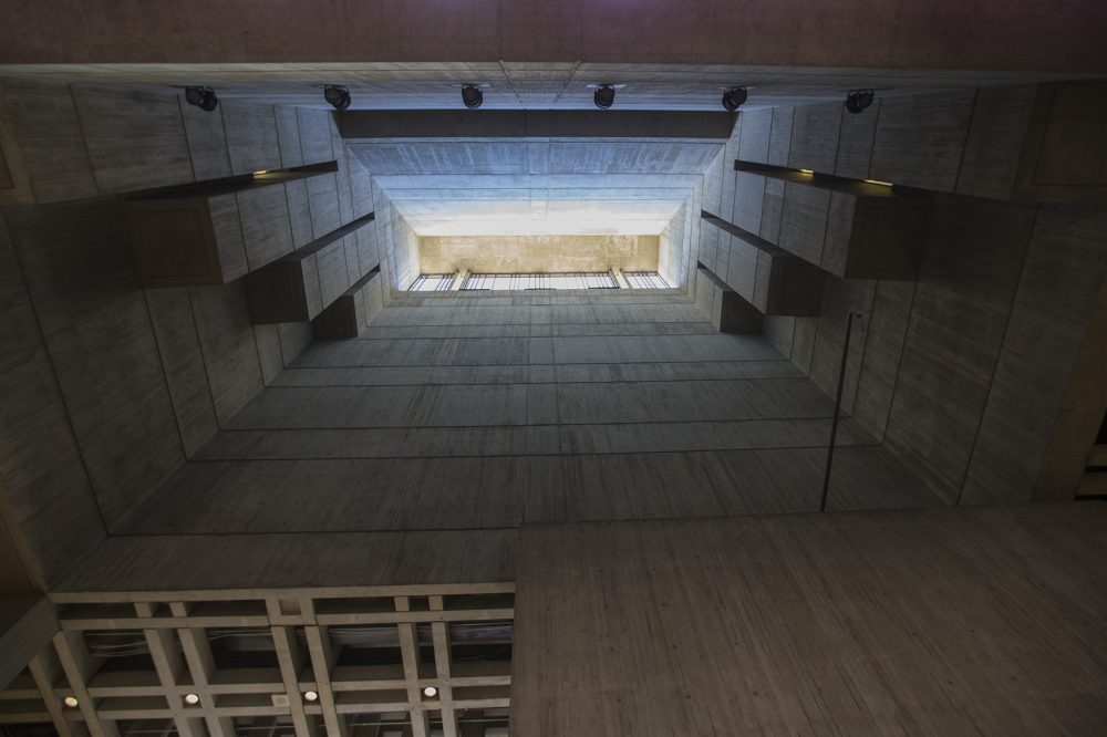 A shaft of sunlight pours in through the concrete walls of Boston City Hall's lobby. (Jesse Costa/WBUR)