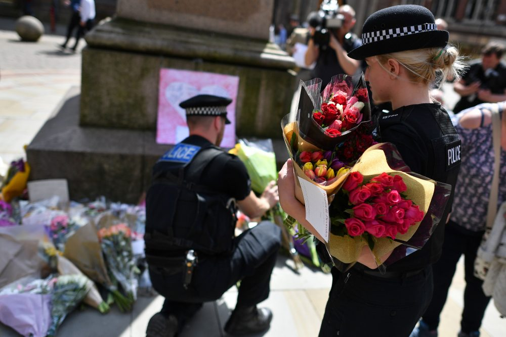Police officers relocate floral tributes in St. Ann's Square in Manchester, northwest England, on May 23, 2017, laid as a mark of respect to those killed and injured following a deadly terror attack at a concert at Manchester Arena the night before. (Ben Stansall/AFP/Getty Images)
