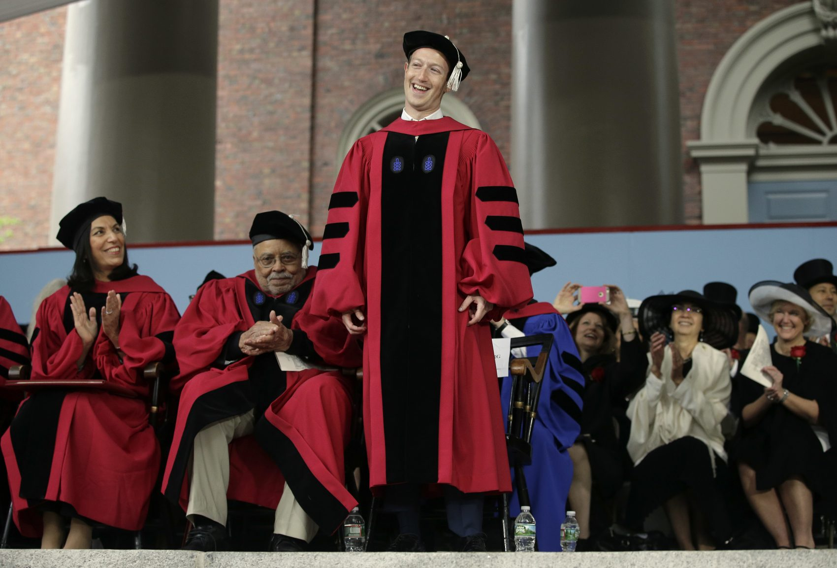 Facebook CEO and Harvard dropout Mark Zuckerberg, center, smiles as he is introduced before being presented with an honorary Doctor of Laws degree during Harvard University commencement exercises Thursday. (Steven Senne/AP)