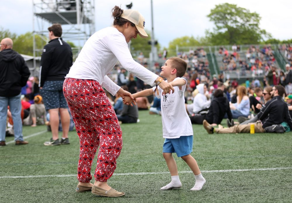 Katie Biello and her son Jude dance near the stage on Sunday. (Hadley Green for WBUR)