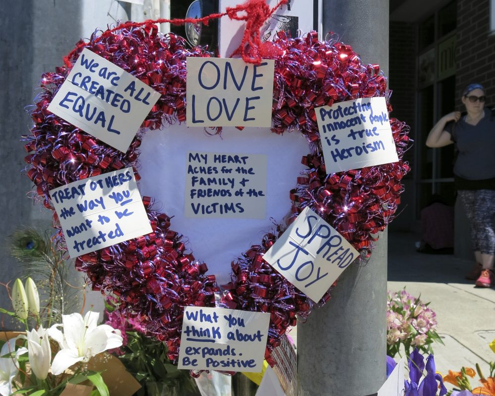 A heart-shaped wreath covered with positive messages hangs on a traffic light pole at a memorial for two bystanders who were stabbed to death Friday, while trying to stop a man who was yelling anti-Muslim slurs and acting aggressively toward two young women, including one wearing a Muslim head covering, on a light-trail train in Portland, Ore, Saturday, May 27, 2017. (Gillian Flaccus/AP)