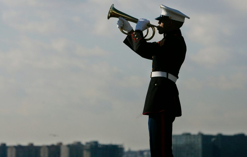 A U.S. Marine Corps bugler plays taps during a ceremony on the USS Intrepid Air and Space Museum in New York City. (Stephen Chernin/Getty Images)