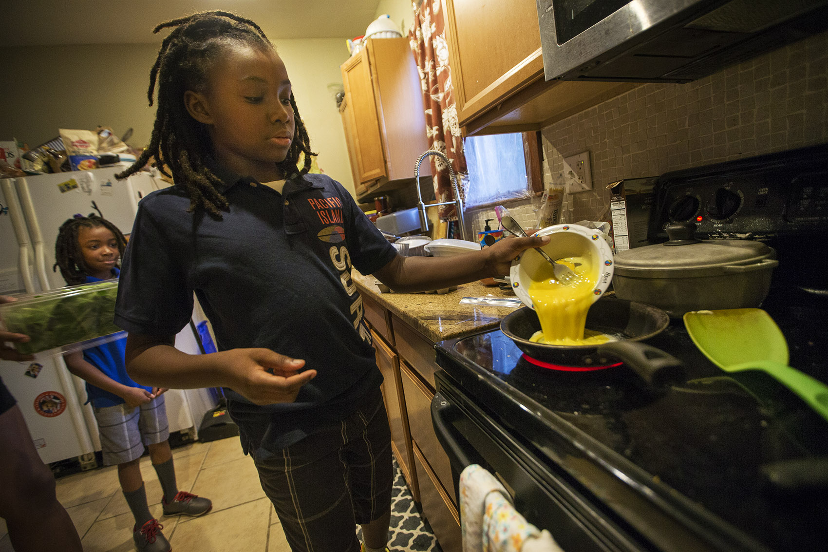 To start the day, Stephen Hilliare makes scrambled eggs for the whole family.(Jesse Costa/WBUR)