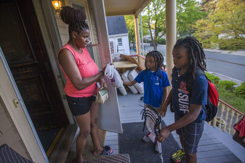 Beverly Hilaire gives her sons snacks for their long ride home from school. (Jesse Costa/WBUR)