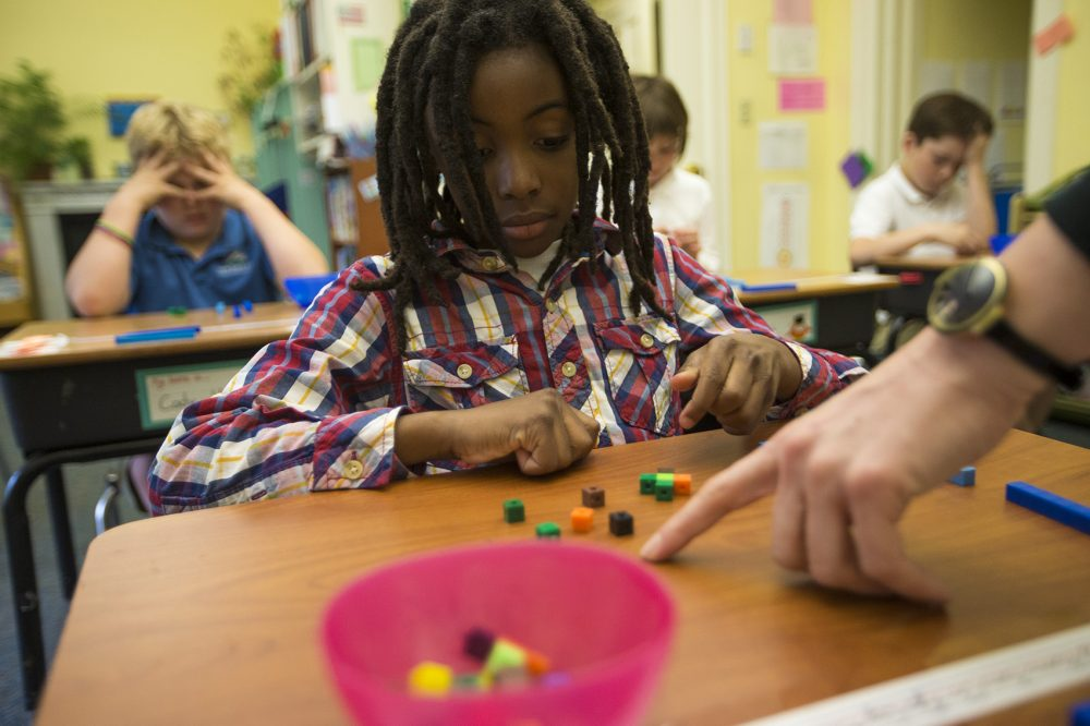 Along with the rest of his class at the Landmark School, 9-year-old Harrison Hilaire does math problems with blocks to help him visualize units. (Jesse Costa/WBUR)