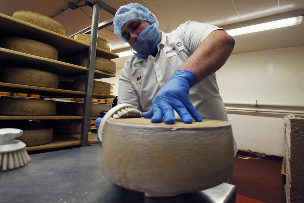 In this Feb. 27, 2017, photo, Nick Brummel prepares a wheel of Grand Cru Surchoix cheese at the Emmi Roth USA production plant in Monroe, Wis, for labeling. The company won the World Championship Cheese Contest in 2016 for the cheese and since then has seen an increase in sales of the cheese. The contest is organized by the Wisconsin Cheese Makers Association, which also organizes the United States Championship Cheese Contest that runs until March 9, in Green Bay, Wis. The contests are in alternate years. (AP Photo/Carrie Antlfinger)