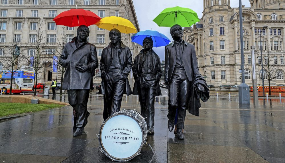 """The sixties produced a glorious body of music that spoke to the era's overheated idol worship, a commentary that still speaks to the Trump phenomenon, writes Tim Riley. In this photo, umbrellas are placed over the statute of the Beatles on Liverpool's waterfront, in Liverpool, England, Wednesday, March 22, 2017. The city is celebrating the half-centenary of """"Sgt. Pepper's Lonely Hearts Club Band,"""" one of the band's most influential albums. (Peter Byrne/ PA via AP)"""