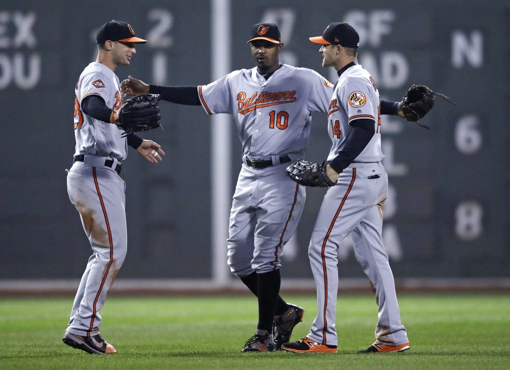 Baltimore Orioles center fielder Adam Jones, center, with teammates during a game at Fenway Park in Boston on Monday. (Charles Krupa/AP)