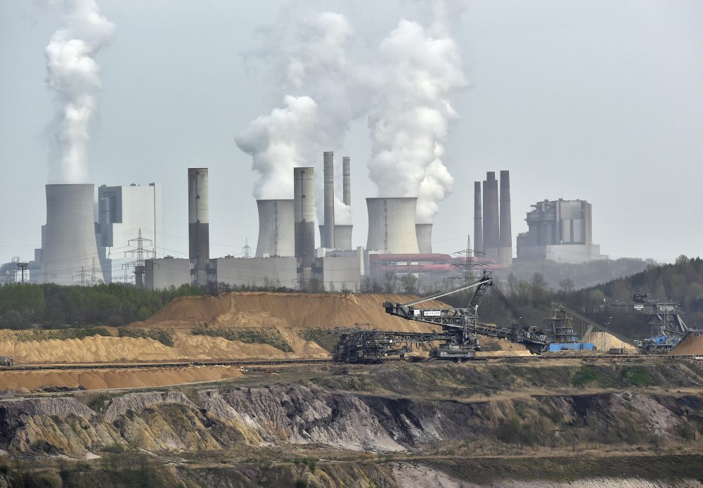 In this 2014 file photo, giant machines dig for brown coal at the open-cast mining Garzweiler in front of a smoking power plant near the city of Grevenbroich in western Germany. (Martin Meissner/AP)