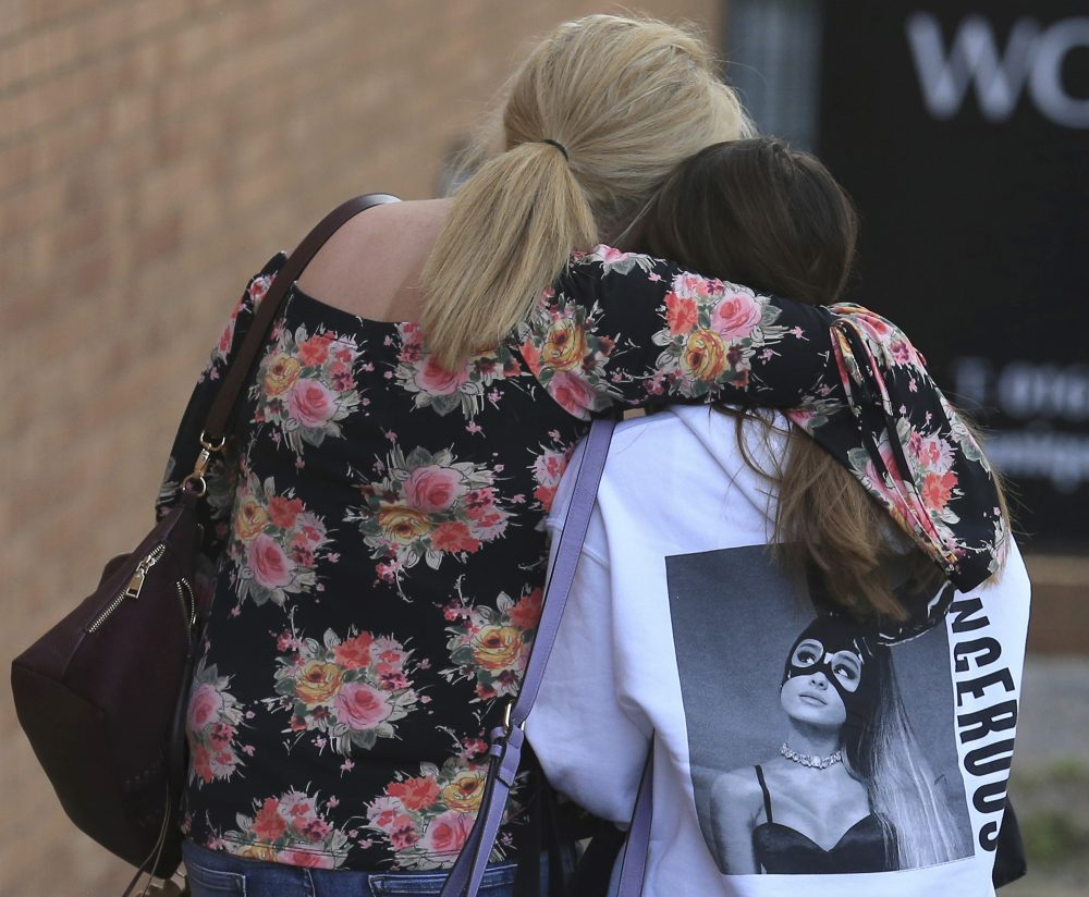 A fan is comforted as she leaves the Park Inn hotel in central Manchester, England on Tuesday. More than 20 people were killed in an explosion following a Ariana Grande concert at the Manchester Arena late Monday evening. (Rui Vieira/AP)