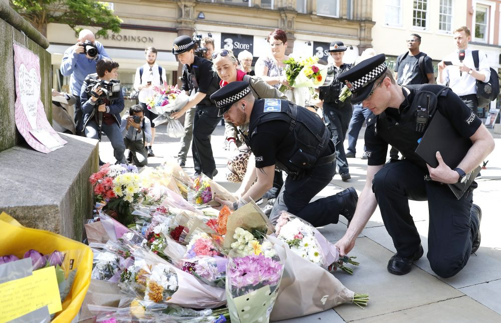 Police officers add to the flowers for the victims of the Monday night concert explosion, in St Ann's Square, Manchester. (Martin Rickett/PA via AP)