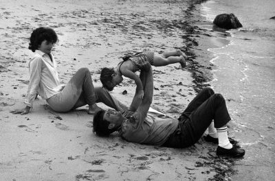 Jacqueline Bouvier Kennedy and John F. Kennedy, who is holding Caroline Kennedy, on a beach in Hyannis Port, Mass. (Courtesy Mark Shaw/John F. Kennedy Presidential Library and Museum in Boston)