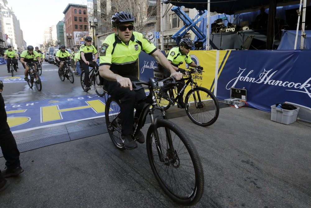Boston police ride through the finish line area before the 121st Boston Marathon on Monday, April 17, 2017. The Police Department says covering special events and challenges with recruitment and retention have lead to an increase in overtime costs, but The Boston Globe analysis tells a different story. (Elise Amendola/AP)