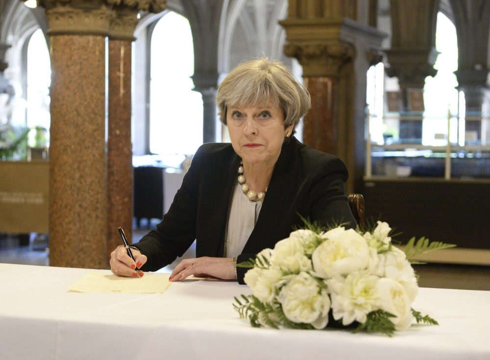 Britain's Prime Minister, Theresa May, writes a message at Manchester Town Hall, Tuesday May 23, 2017. (Ben Birchall/AP)